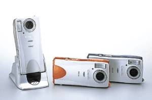 Ricoh's Caplio  RR10 digital camera, with silver-trim version in dock, and blue/orange trim versions alongside. Courtesy of Ricoh.