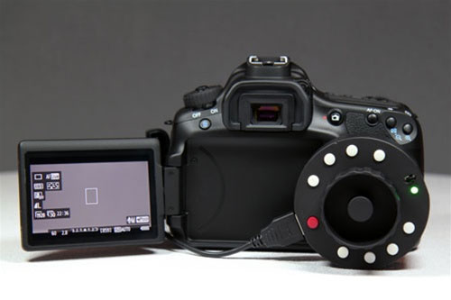 The Okii USB Follow Focus controller alongside a Canon DSLR for scale. Photo provided by Okii Systems LLC.