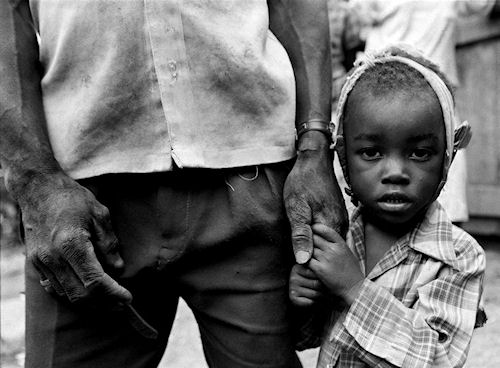 There was a tiny hamlet, maybe six hours outside Port au Prince, filled with the ghosts of small children. The whole area, not just the village, had been isolated by the Cedras regime, and now three-quarters of the town's children had died in a mumps epidemic. Their parents had voted for Aristide in the previous election, and those votes -- officially registered in Port au Prince -- had cost them dearly under the current military dictatorship. Add the U.S. embargo, and the people were virtually cut off from the capitol. The village leader had lost three children of his own; two in one day, and a third he had carried on his back all the way down a long, treacherous road to a health clinic that had been closed. The military, weeks before, had cleared out all medicine and equipment and taken it back to Port au Prince -- more punishment for their Aristide vote. He made the long trek back to his village -- with child on his back -- where she later died. Now his son -- his last child -- was sick. This portrait shows this child clutching the hand of his father. My eyes locked with the village leader for quite some time and knew what he said was very important. I asked my interpreter what he said and his response was, 'please tell the world we are the ones who are suffering.' Photo copyright ©2010, Colin Finlay. Photo and caption provided by Western Digital Corp. Click for a bigger picture!