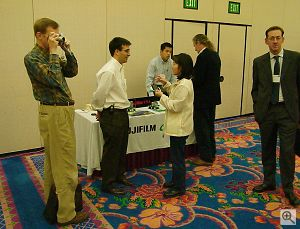 Fuji's Andy Laguardia talks to an attendee as our own Dave Etchells examines the new FinePix 2800 Zoom digital camera. Copyright © 2001, Michael R. Tomkins. All rights reserved. Click for a bigger picture!