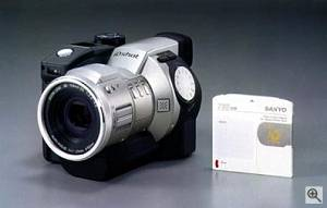 Sanyo's iDshot IDC-1000Z digital camera, front left quarter view with iD PHOTO disk. Courtesy of Sanyo - click for a  bigger picture!
