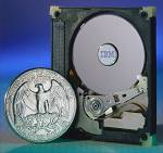 IBM's MicroDrive shown with case opened alongside a United States quarter for size comparison. Courtesy of IBM.