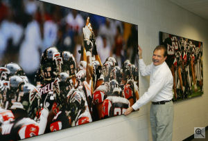 Pete Casabonne, President of Myphotopipe.com, stands next to one of the company's 4,608-square-inch prints made for the Atlanta Falcons football team.