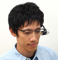 Mobile spectacle-type wearable retinal imaging display shown in use. Photo provided by Brother Industries Ltd.