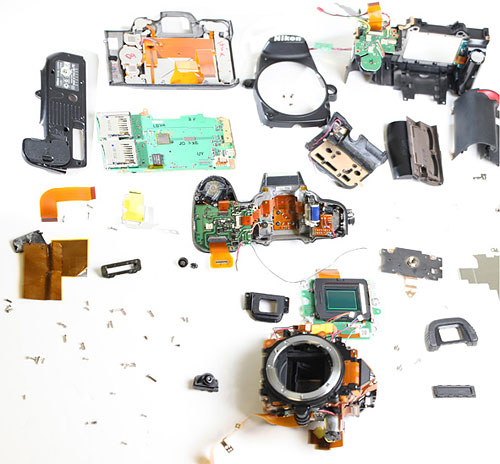 Parts after preliminary disassembly. The mirror box, top assembly, and LCD/back assembly are not disassembled yet. Photo copyright © 2012, Roger Cicala. Used by permission.